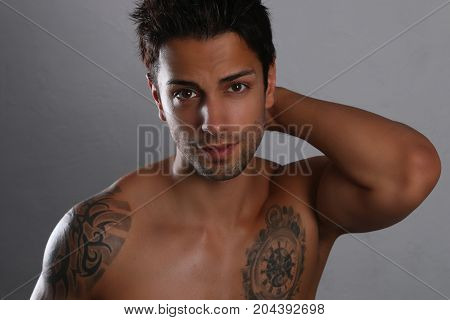 Sexy male posing shirtless on a gray background
