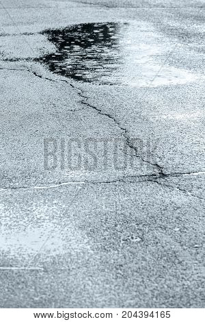 Wet Cracked Asphalt Sidewalk With Water Puddles And Raindrops