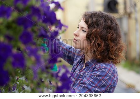 happy female nursery worker trimming plants in greenhouse poster