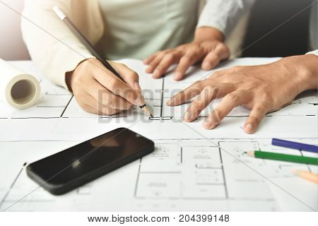 Close up Creative Designers brainstorming Interior Architecture projects with sketch on paperwork.