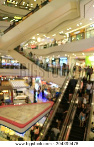 Vertical image of blurred shopping mall with so many people on the escalators