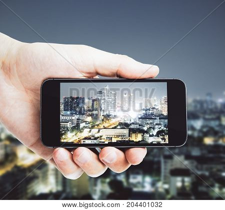 Male hand taking photograph of night city with cellphone