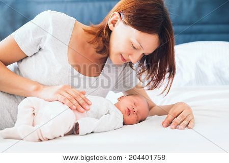 Young mother looking on her newborn baby. Beautiful mom lying at bed with a cute sleeping new born child. Baby's first days of life in family at home.