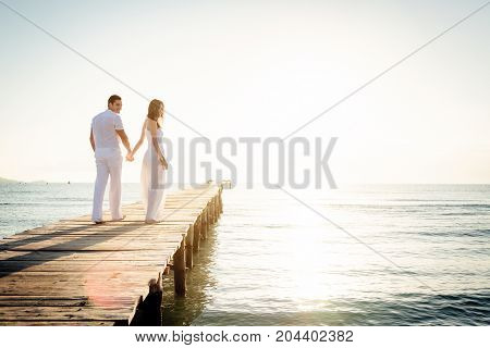 young couple walking on pier with the sun rising over the mediterranean sea