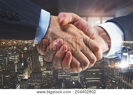 Side view of creative handshake on night city background. Team concept. Double exposure