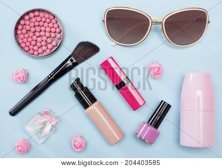 Modern urban woman essentials: foundation, blush, lipstick, deodorant, perfume, nail polish, sunglasses. Contents of cosmetic bag