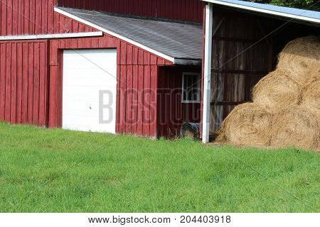 Red and white barn with detached round hay bale storage and green field,