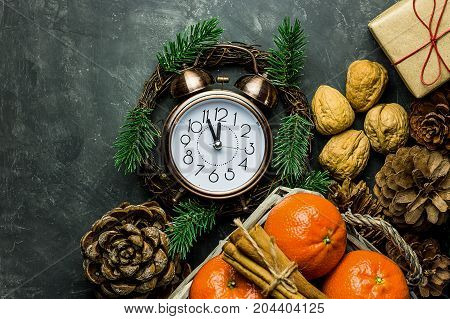 Vintage alarm clock set to five minuted to midnight. New Year's eve countdown. Pince cones walnuts tangerines cinnamon sticks gift box in craft paper. Christmas greeting card poster. Copy space