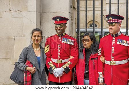 London - May 2016: tourists, taking photos with the royal guards near Whitehall