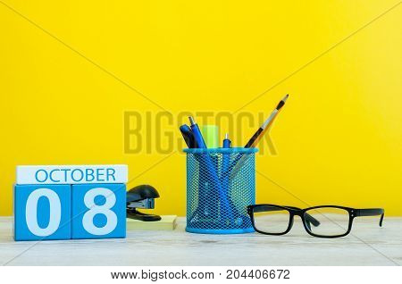 October 8th. Day 8 of month, wooden color calendar on teacher or student table, yellow background . Autumn time. Empty space for text.