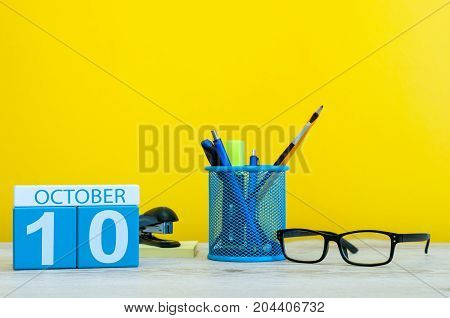 October 10th. Day 10 of month, wooden color calendar on teacher or student table, yellow background . Autumn time. Empty space for text.