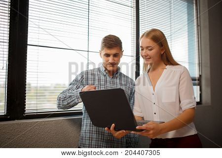 Young coworkers working together in modern coworking studio. Woman using laptop and talking with colleague about new startup project. Horizontal.