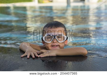 A happy young boy relaxing on the side of a swimming pool wearing goggles