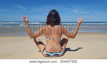 Rear View Portrait Of Young American Woman Sitting At Beach In Yoga Pose