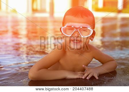 A happy young boy relaxing on the side of a swimming pool wearing goggles. Toned