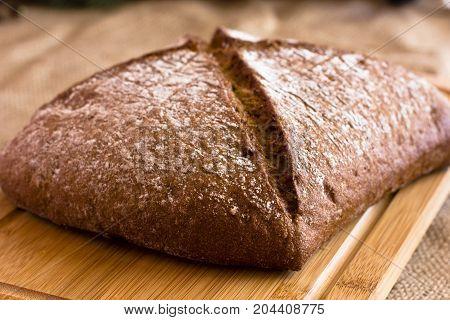 Rye Dark Bread On A Wooden Platter On Burlap