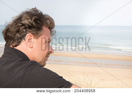 Unhappy Man Thinking Sitting In Front Of The Sea