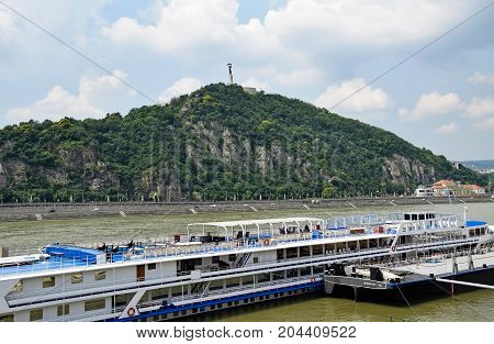 Tourist ship on the river Danube and the Gellert hill, Budapest, Hungary