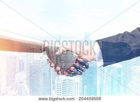 Close up of a businessman in a suit and a robot shaking hands. Foggy cityscape background. Concept of innovation in business. Toned image double exposure