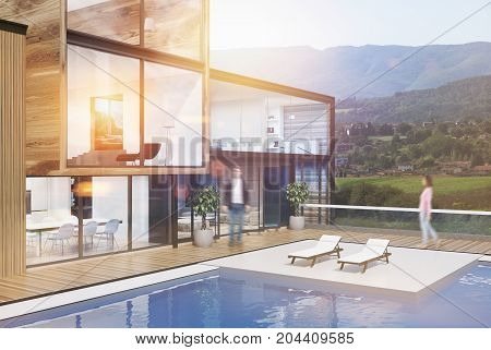 Side view of a wooden and glass wall mansion with a luxury swimming pool. There are two deck chairs in the yard. 3d rendering mock up toned image