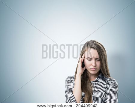 Portrait of a young woman with long fair hair. She is wearing a striped shirt and having a strong headache. Gray background. Mock up