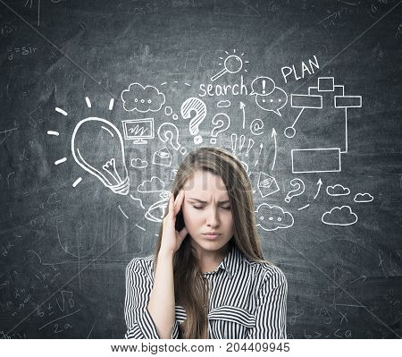 Portrait of a young woman with long fair hair. She is wearing a striped shirt and having a strong headache. Blackboard with a business plan sketch