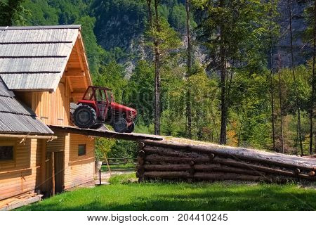 Rustic old red tractor on ramp of wooden barn, woods and mountains in background