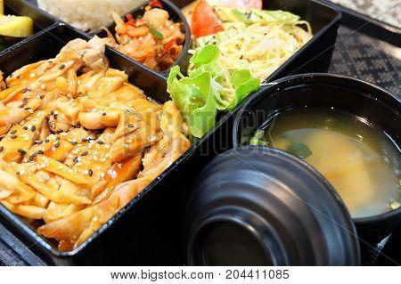 Traditional Japan Cuisine Bento Box or Multi-Layered Box with Teriyaki Chicken Rice Salad Tamagoyaki or Rolled Omelette Hiyashi Wakame or Seaweed Salad and Kimchi.
