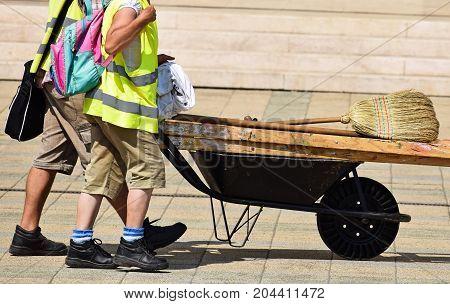 Men pushing a wheelbarrow on the street