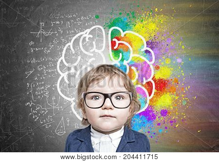 Close up portrait of a cute little boy in a blue business suit standing near a blackboard with formulas and a colorful brain sketch on it.