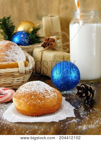 Donuts berliner and a glass of milk surrounded by Christmas attributes