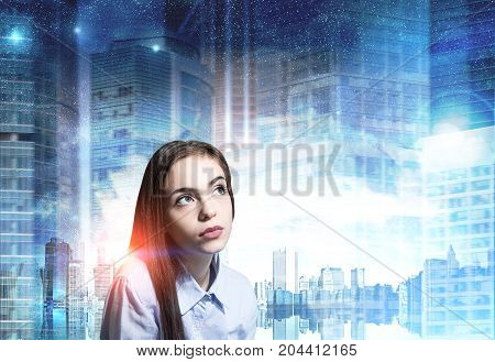 Portrait of a dreamy young woman with full lips and long fair hair. She is looking upwards and thinking against a blue cityscape background. Mock up