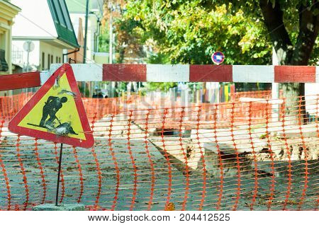 Work ahead street reconstruction site with sign and fence as road barricade