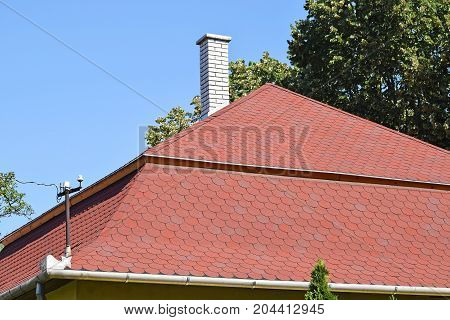 Roof of a building with shingle and smoke stack