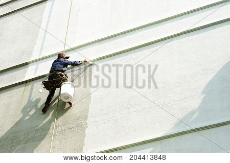 painter hanging on white building , painter worker