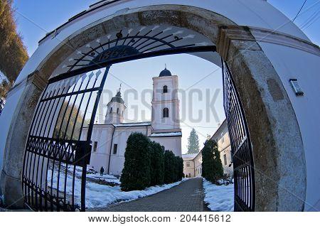 Entrance to Beocin monastery covered with snow at sunny winter morning, near Novi Sad, Serbia