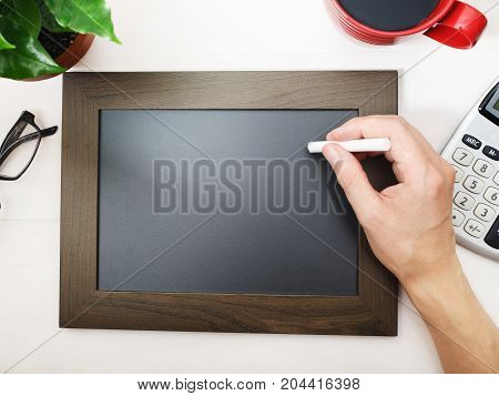 Man sketching on a blank blackboard with coffee and calculator