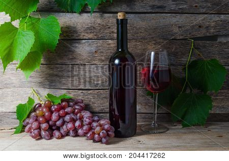 Grape Vine wine bottle and glass with wine on a background of green foliage and old wooden boards