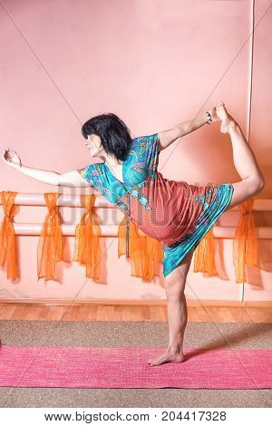 Healthy lifestyle maternity concept. 40 week pregnant middle aged caucasian woman wearing dress standing on the one leg in asana doing yoga exercises.
