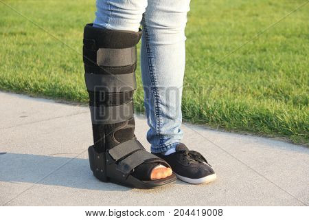 A woman standing with a walking cast boot