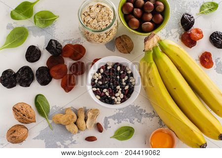 Products rich of potassium - K. Bananas, spinach, nuts, grains, dried fruits overs stone table. Space for text