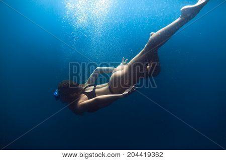 Slim woman swimming in sea. Underwater view