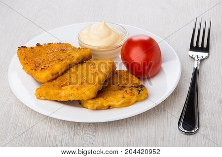 Fish In Breadcrumbs, Mayonnaise, Tomato On White Plate And Fork