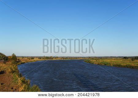 The Limpopo River in flat land of Mozambique the coasts are red and dry the sky clean and blue