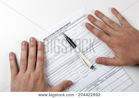 human hand and the form of the document application for employment