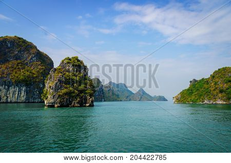 Halong Bay cruise view (Descending Dragon Bay) at the Gulf of Tonkin of the South China Sea Vietnam. Landscape formed by karst towers-isles on blue sky background.