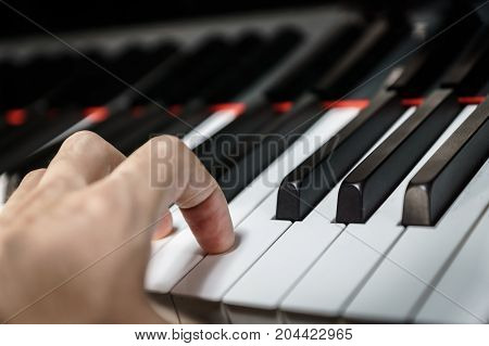Piano keys on black classical grand piano with hand playing chord