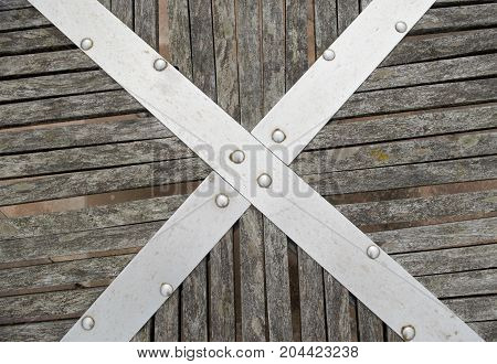 Studded Metal Cross Securing Aged Wooden Planks