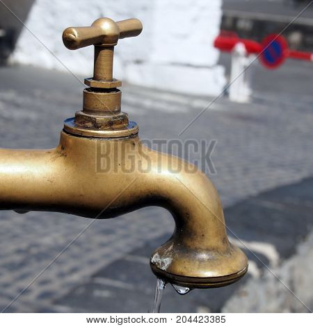 brass dripping tap or faucet in a public street