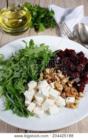 Ingredients for the preparation of salad from roasted beets arugula cheese feta and walnuts. Vertical shot. View from above.